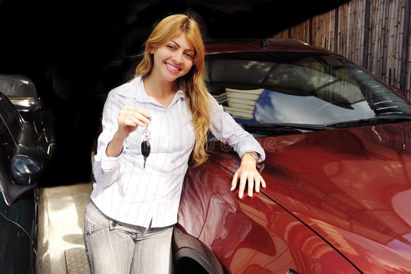 Donna che mostra tasto di nuova automobile rossa immagine stock libera da diritti