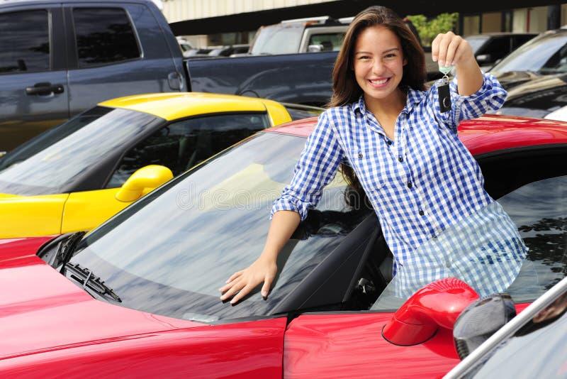Donna che mostra tasto di nuova automobile sportiva immagini stock