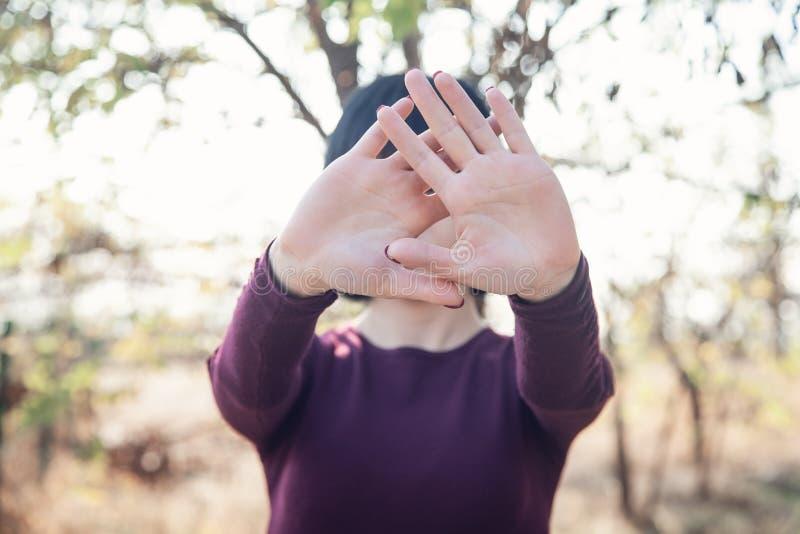 Donna che nasconde il suo fronte e che mostra gesto di arresto in all'aperto Concetto di violenza immagine stock libera da diritti