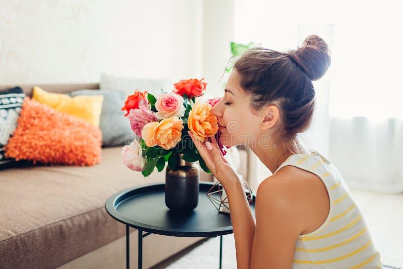 Donna che odora le rose fresche in vaso sulla tavola Casalinga che prende cura di comodit? in appartamento Interno e decorazione fotografia stock
