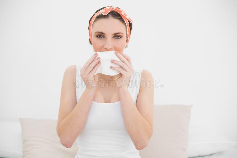 Donna che odora su un fazzoletto che esamina la macchina fotografica fotografie stock