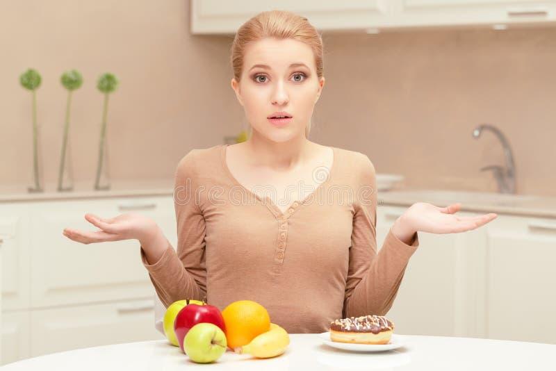 Donna che opera scelta fra frutta e la ciambella immagini stock
