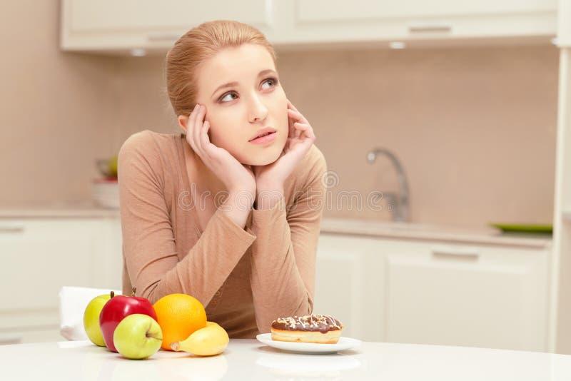 Donna che opera scelta fra frutta e la ciambella fotografia stock