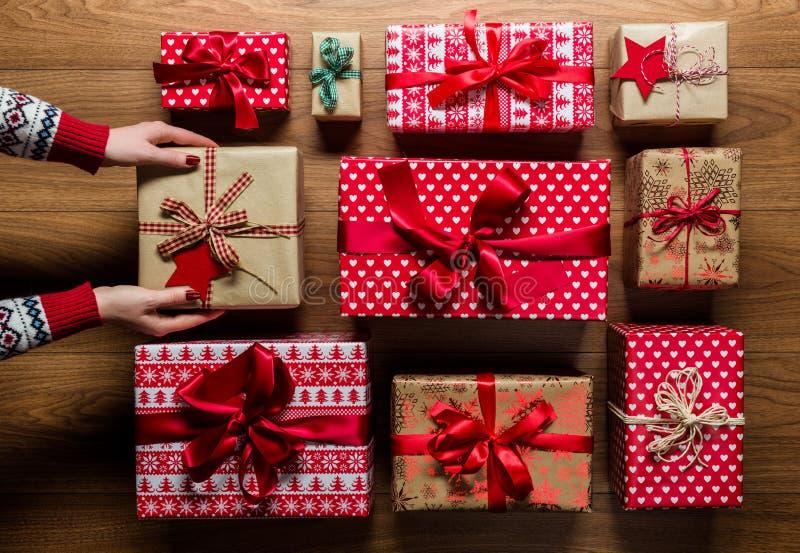 Donna che organizza i regali di Natale d'annata beautifuly avvolti su fondo di legno fotografie stock