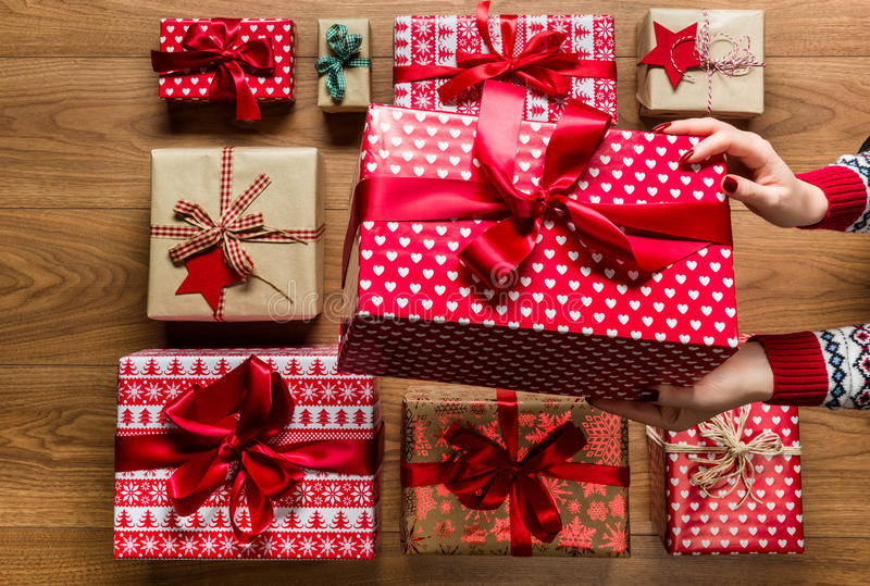Donna che organizza i regali di Natale d'annata beautifuly avvolti su fondo di legno immagine stock libera da diritti