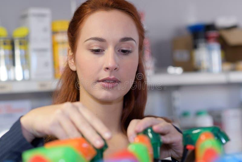 Donna che organizza lo spruzzo variopinto delle bottiglie sullo scaffale fotografia stock