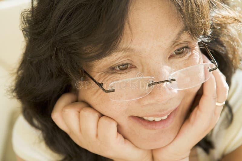 Donna che osserva attraverso i nuovi vetri immagine stock