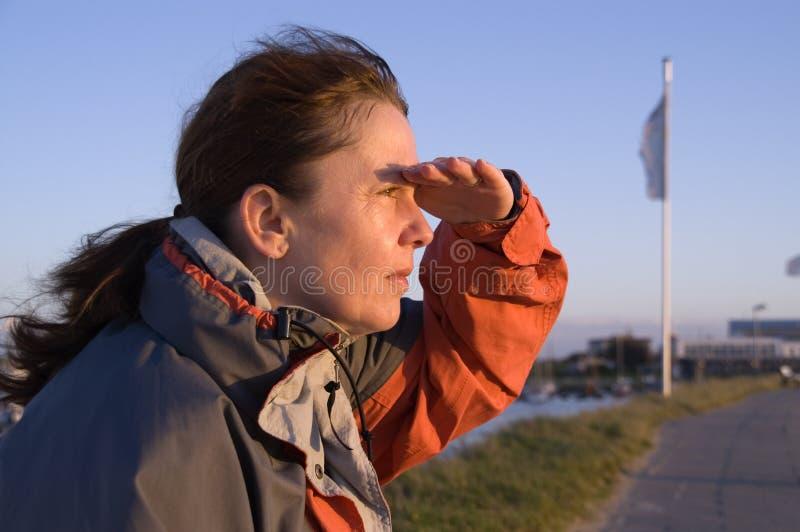 Donna che osserva fuori al mare fotografia stock libera da diritti