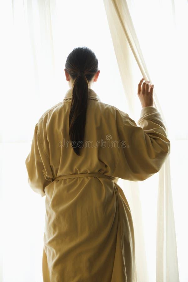 Donna che osserva fuori finestra. fotografia stock libera da diritti