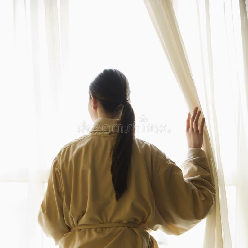 Donna che osserva fuori finestra. immagine stock libera da diritti