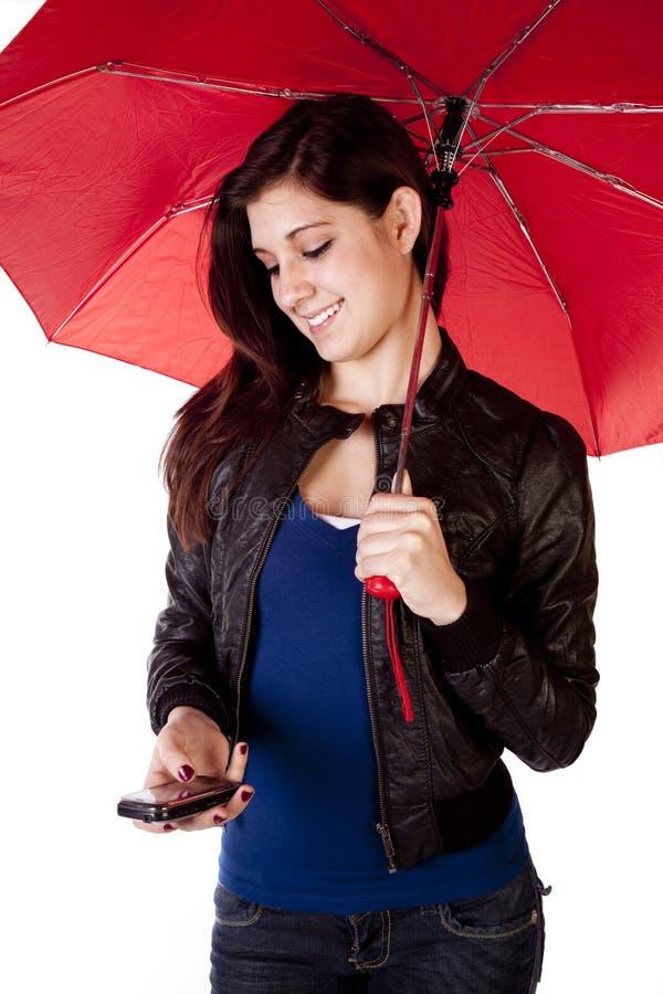 Donna che osserva giù l'ombrello del telefono immagini stock libere da diritti