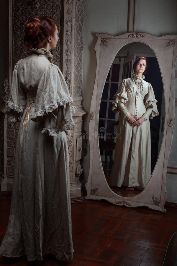 Donna che osserva nello specchio immagine stock