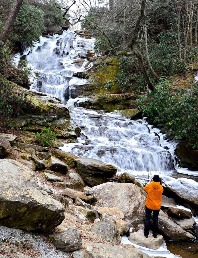 Donna che osserva una cascata congelata fotografia stock