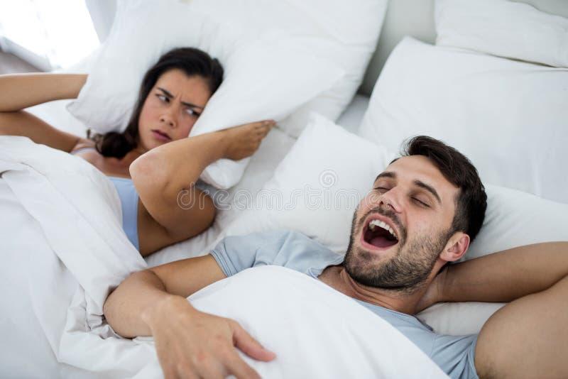 Donna che ottiene di disturbo con l'uomo che russa sul letto immagine stock