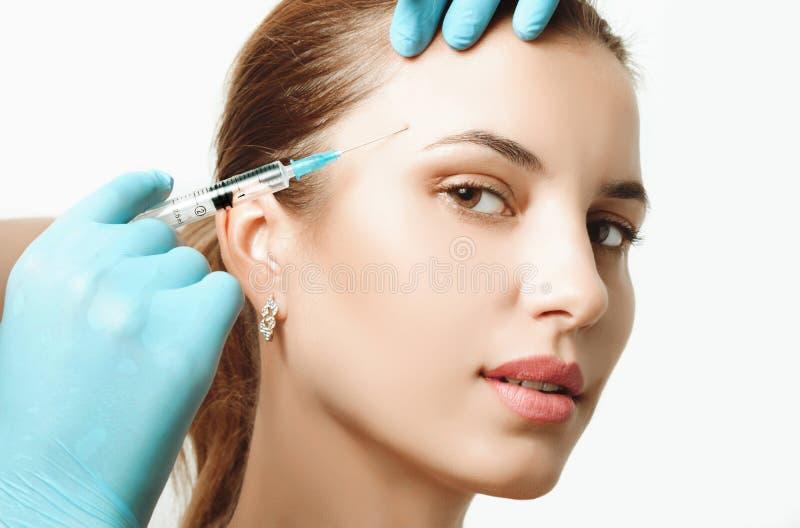 Donna che ottiene iniezione cosmetica di botox in guancia, primo piano immagine stock