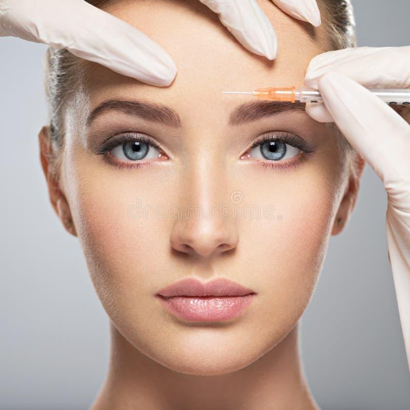 Donna che ottiene l'iniezione cosmetica del botox in fronte immagine stock