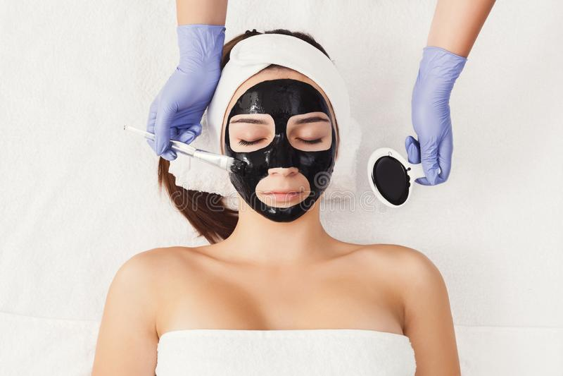 Donna che ottiene la maschera di protezione dall'estetista alla stazione termale immagine stock
