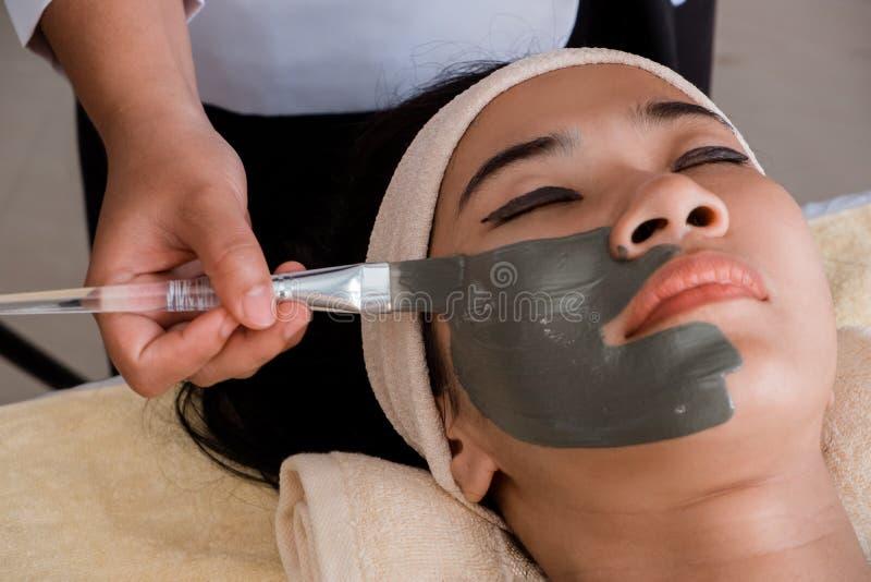 donna che ottiene la sua copertura del fronte con la maschera del fango fotografia stock