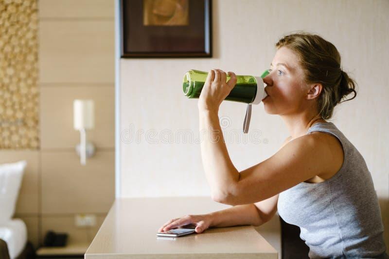 Donna che ottiene mangiante il suo frullato verde dopo la formazione fotografia stock