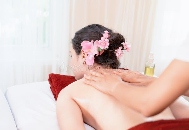 Donna che ottiene massaggio dell'olio su lei indietro nella stazione termale tailandese fotografie stock