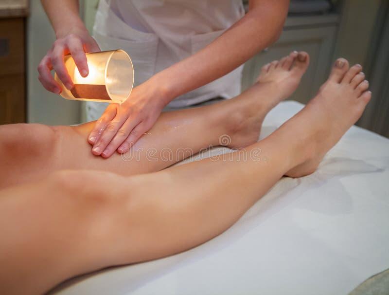 Donna che ottiene massaggio della stazione termale con la candela di massaggio fotografia stock