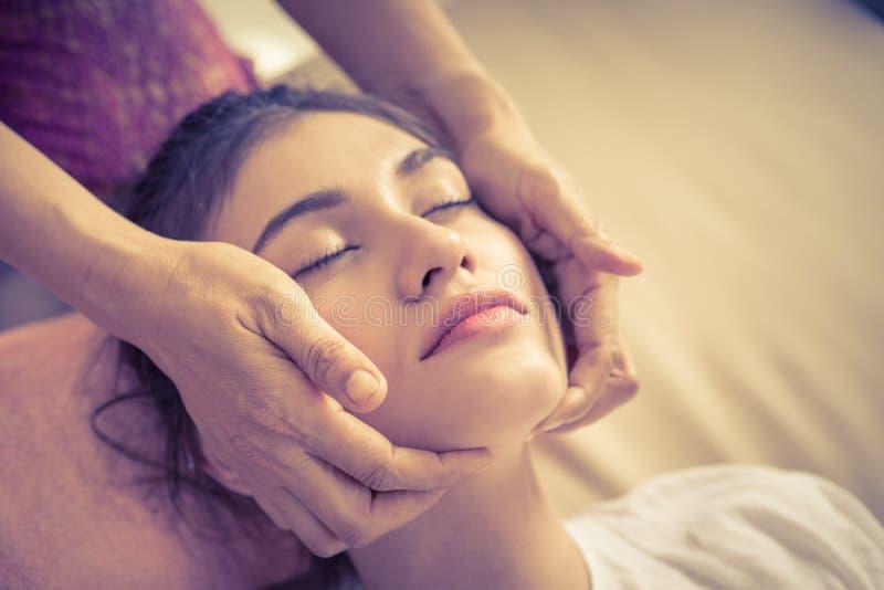 Donna che ottiene massaggio della testa e del fronte nella stazione termale tailandese di massaggio fotografia stock