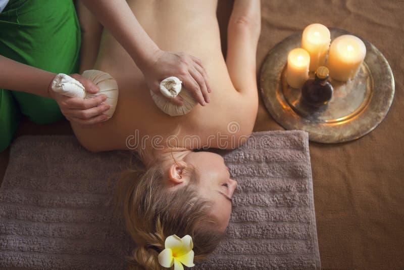 Donna che ottiene massaggio di erbe tailandese della compressa in stazione termale fotografia stock libera da diritti