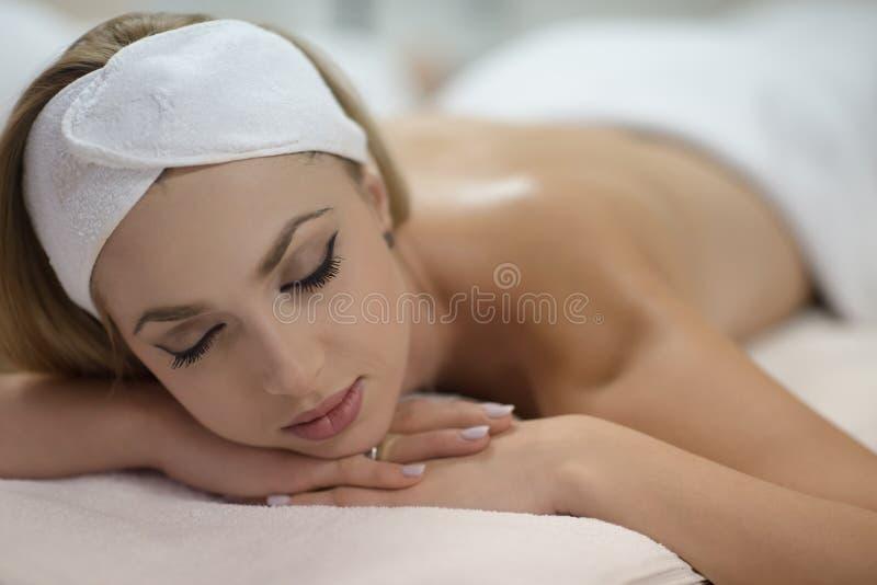 Donna che ottiene massaggio posteriore nel salone della stazione termale fotografia stock