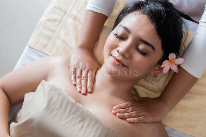 Donna che ottiene massaggio sulla sua spalla fotografie stock libere da diritti