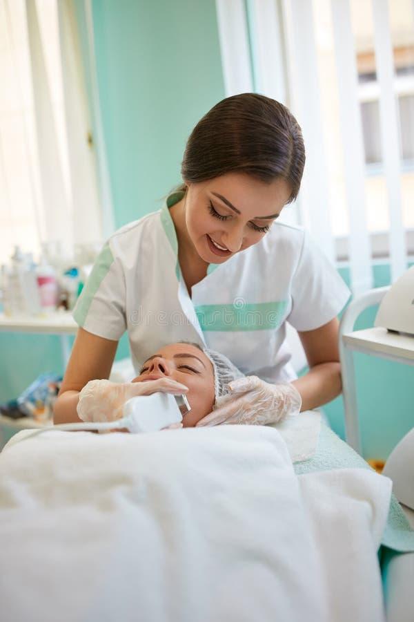Donna che ottiene pulizia della pelle di ultrasuono al salone di bellezza fotografia stock libera da diritti
