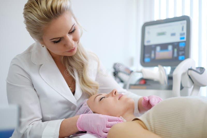 Donna che ottiene trattamento con il dispositivo estetico di dermatologia immagine stock libera da diritti