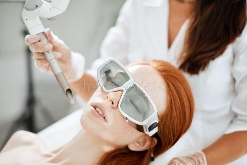 Donna che ottiene trattamento del fronte del laser nel centro medico, concetto di ringiovanimento della pelle fotografie stock
