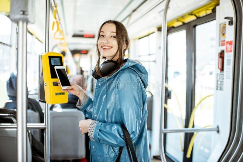 Donna che paga con il telefono il tarnsport pubblico immagine stock