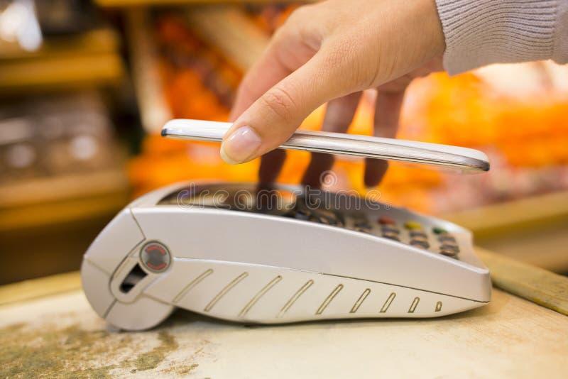 Donna che paga con la tecnologia del nfc sul telefono cellulare, acquisto, supe immagini stock libere da diritti