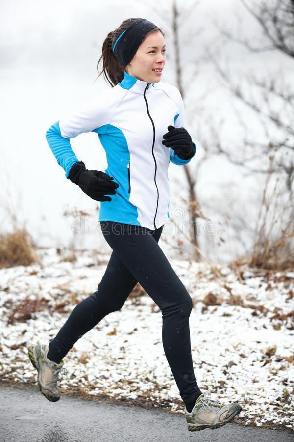 Donna che pareggia in un paesaggio nevoso fotografia stock libera da diritti