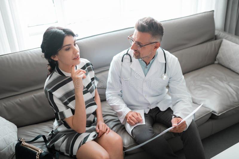 Donna che parla al chirurgo plastico che ha desiderio per correggere mento immagini stock libere da diritti