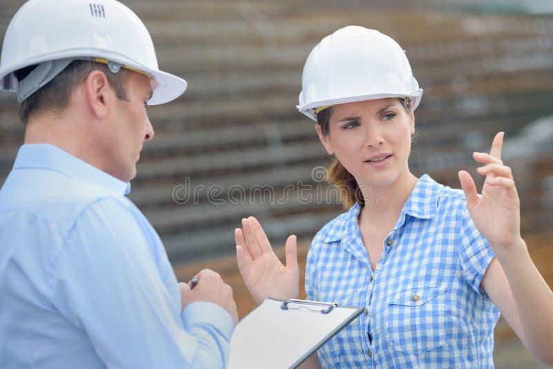 Donna che parla con collega che gesturing con le mani immagine stock libera da diritti