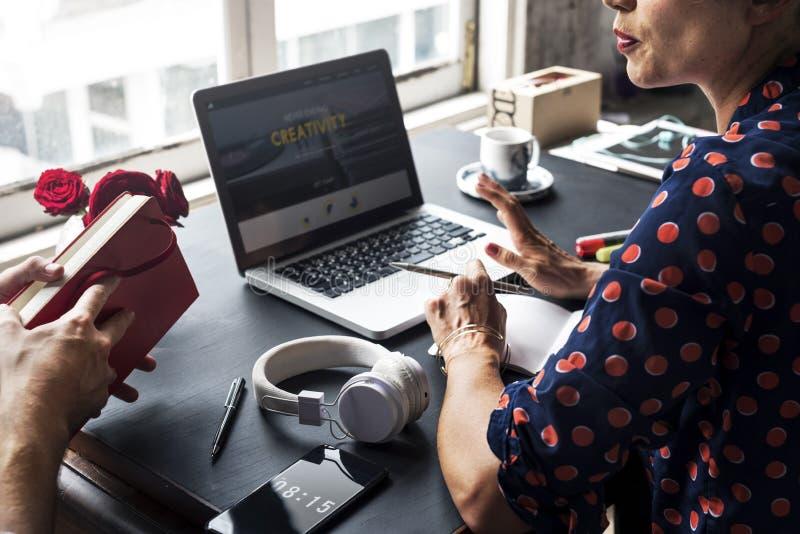 Donna che parla con il collega e che per mezzo del computer portatile immagine stock libera da diritti