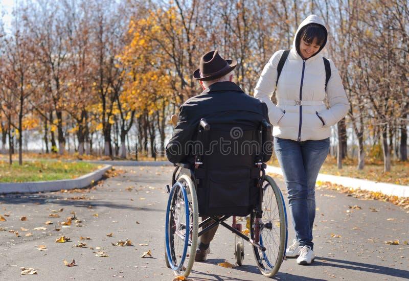 Donna che parla con uomo disabile in una sedia a rotelle fotografia stock