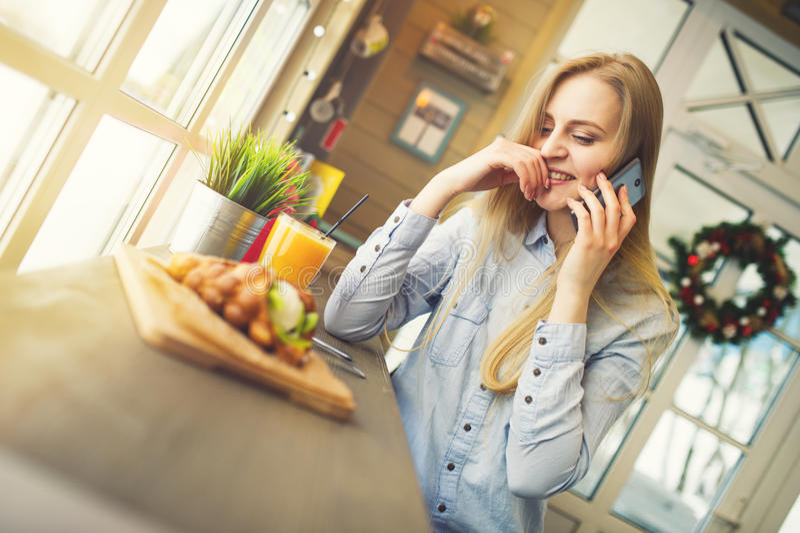 Donna che parla di qualcosa su un telefono cellulare mentre sedendosi ad una tavola in un caffè accogliente di Natale fotografia stock