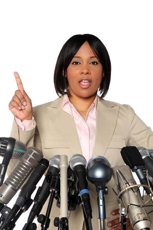 Donna che parla dietro i microfoni fotografia stock libera da diritti