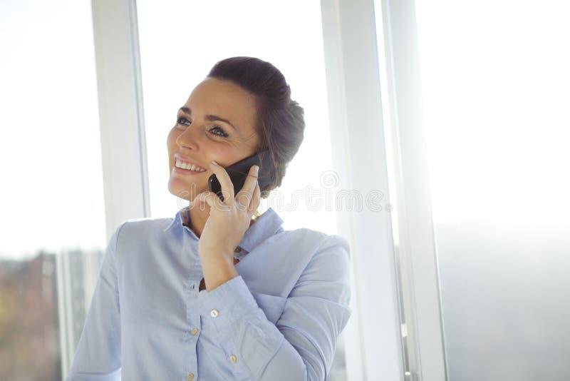Donna che parla in smartphone moderno immagini stock libere da diritti