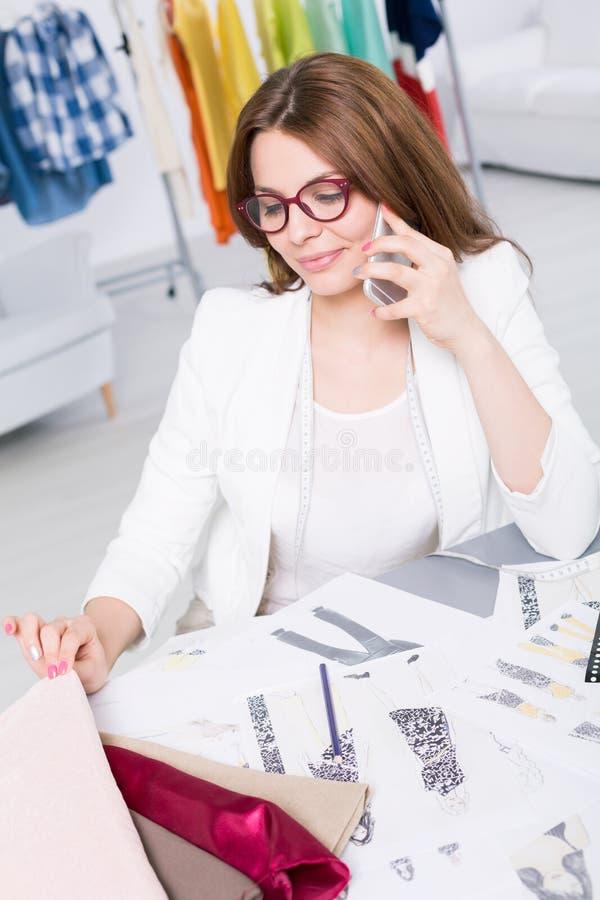 Donna che parla su un telefono mentre esaminando i suoi progetti fotografia stock libera da diritti
