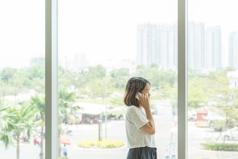 Donna che parla sul cellulare vicino al fondo della finestra fotografie stock