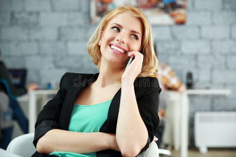 Donna che parla sul telefono all'ufficio immagine stock