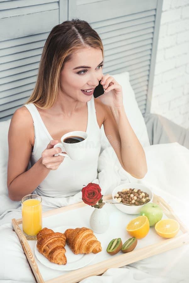 Donna che parla sullo smartphone nel letto immagine stock