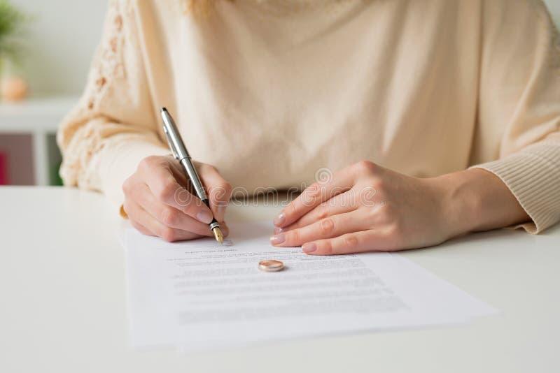 Donna che passa attraverso il divorzio e le carte di firma fotografia stock