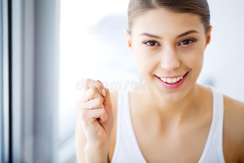 Donna che per mezzo dei denti che imbiancano striscia per il bello sorriso bianco Hig fotografie stock