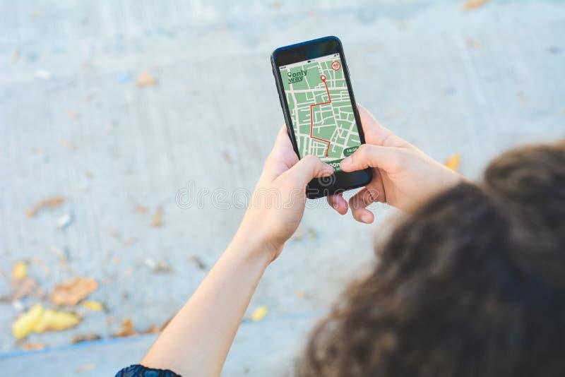 Donna che per mezzo del app di navigazione della mappa di GPS con l'itinerario previsto fotografie stock