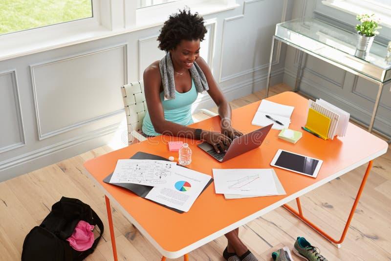 Donna che per mezzo del computer a casa dopo l'esercitazione, visualizzazione elevata fotografie stock libere da diritti